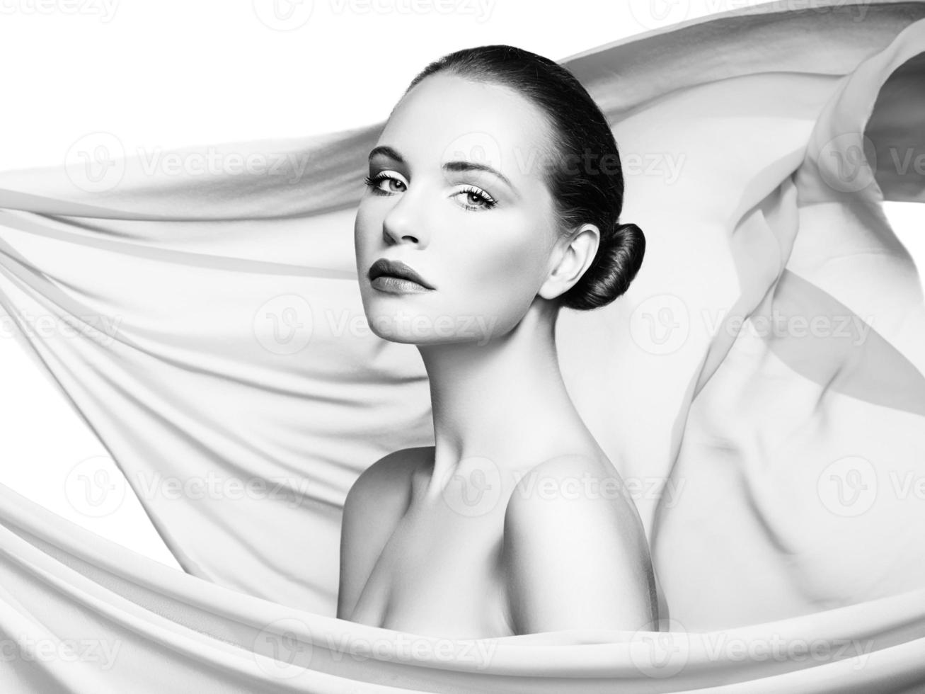 Portrait of young beautiful woman against flying fabric. Beauty photo