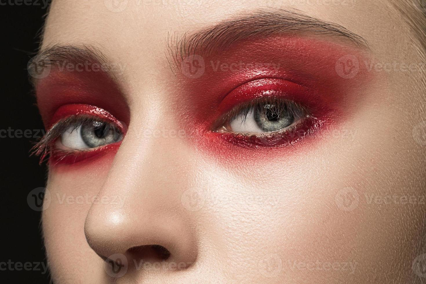 lindo rosto feminino jovem com maquiagem vermelha brilhante foto