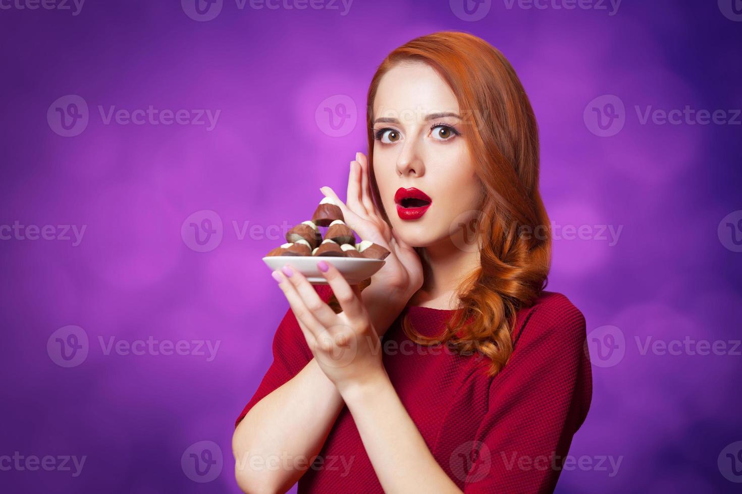 mujeres pelirrojas con dulces sobre fondo violeta. foto