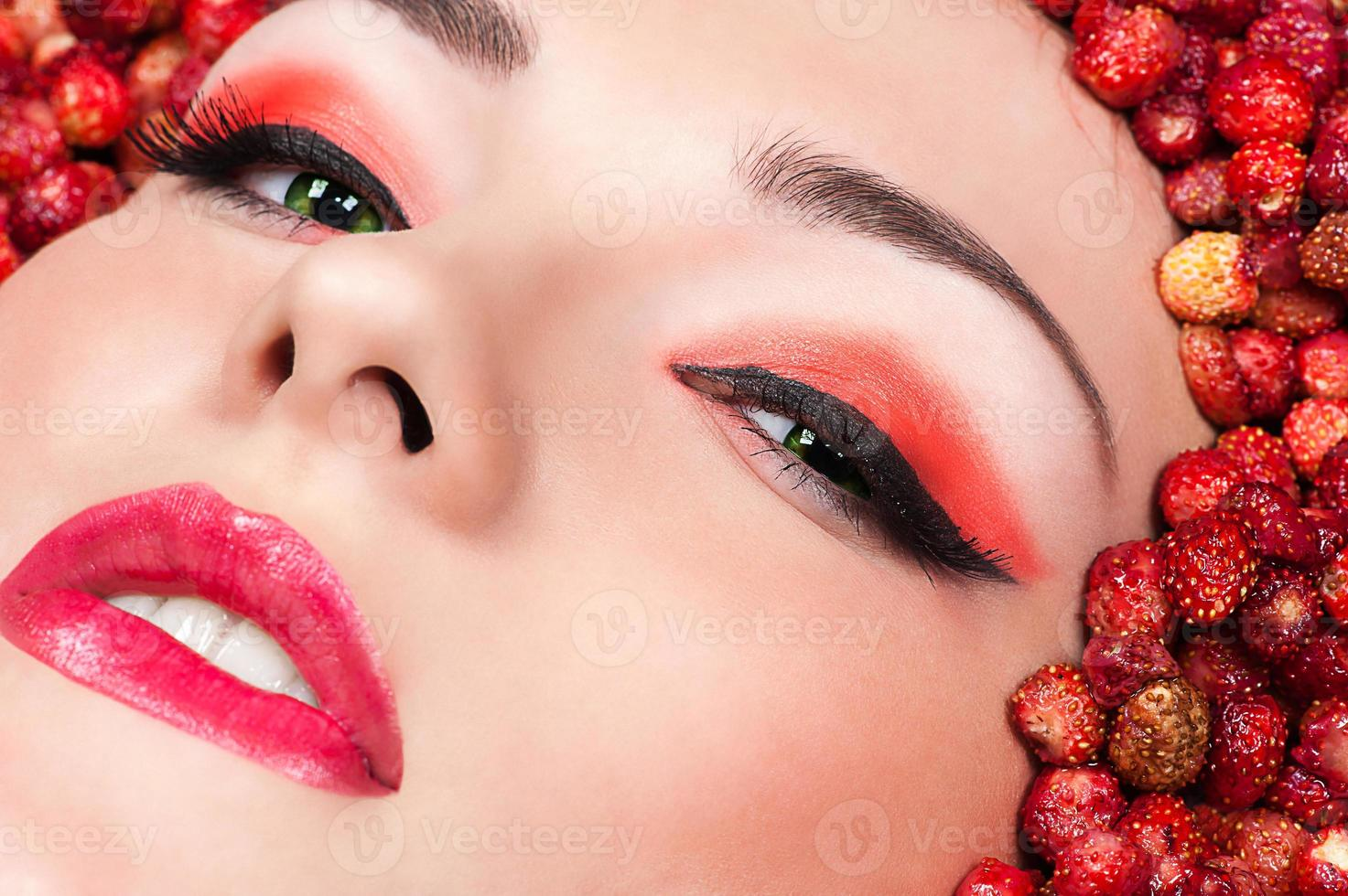 woman in wild strawberry closeup photo