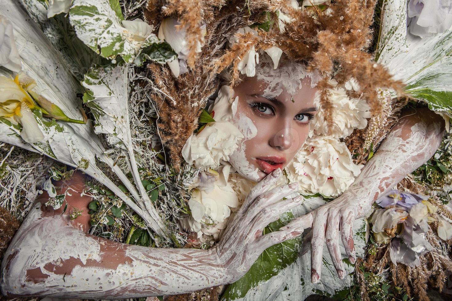 Retrato de niña de cuento de hadas rodeado de flores y plantas naturales. foto