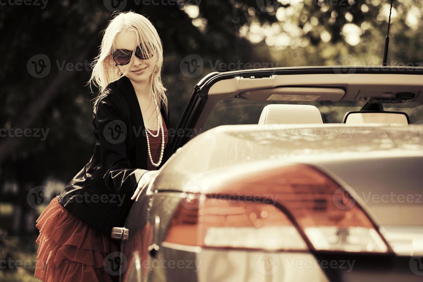 Mujer de moda joven feliz en el coche convertible foto