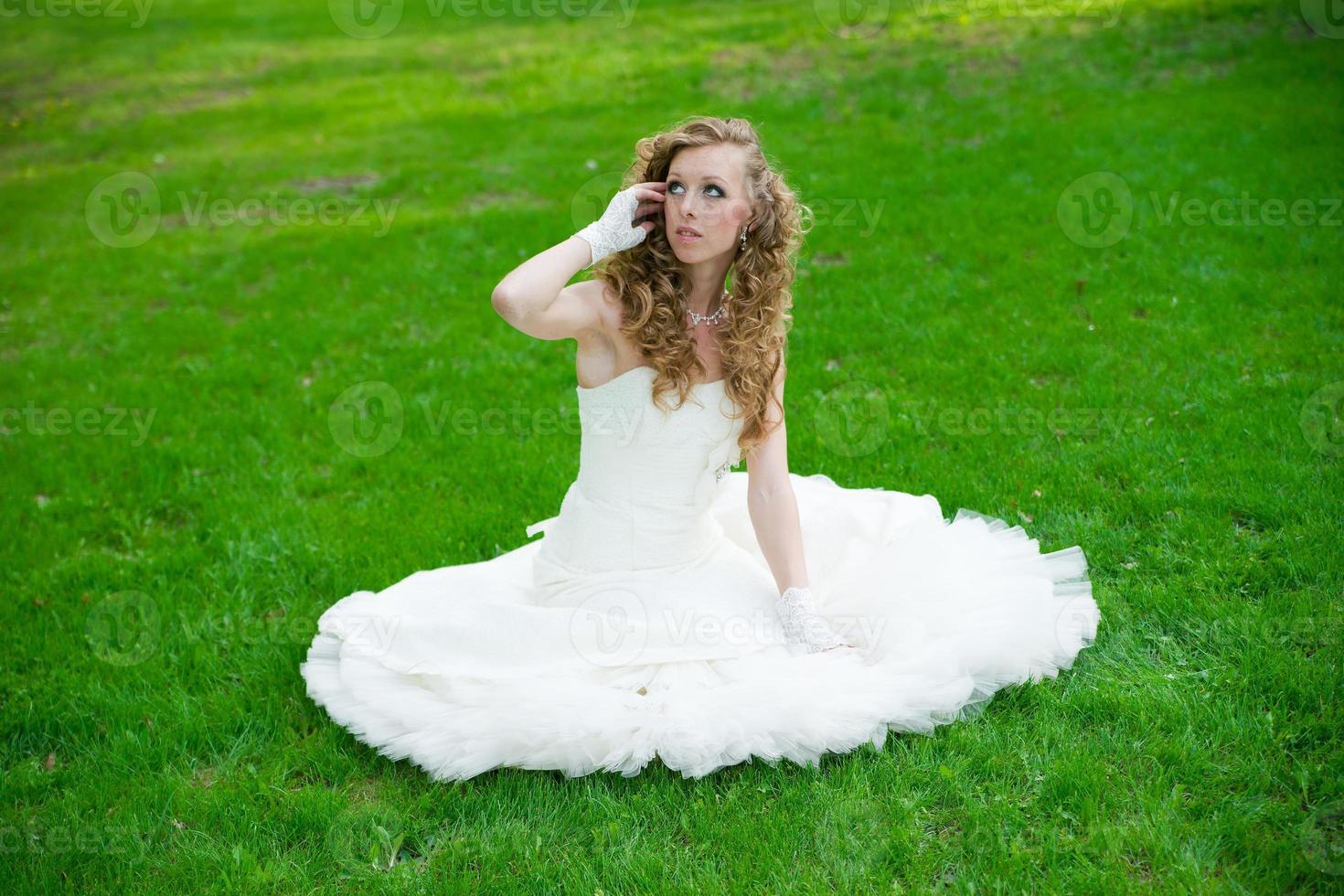 Hermosa novia con un vestido blanco sobre la hierba verde foto