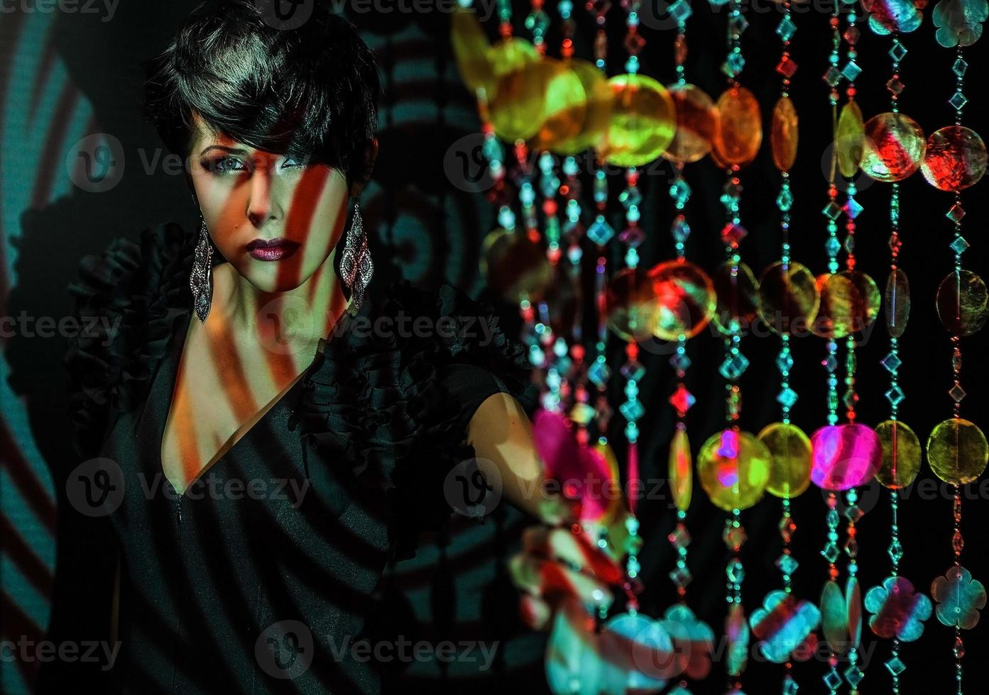 Beautiful brunette woman pose on colorful projector light in studio. photo