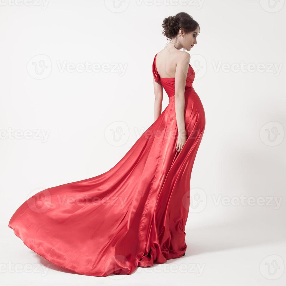 Young beauty woman in fluttering red dress. White background. photo
