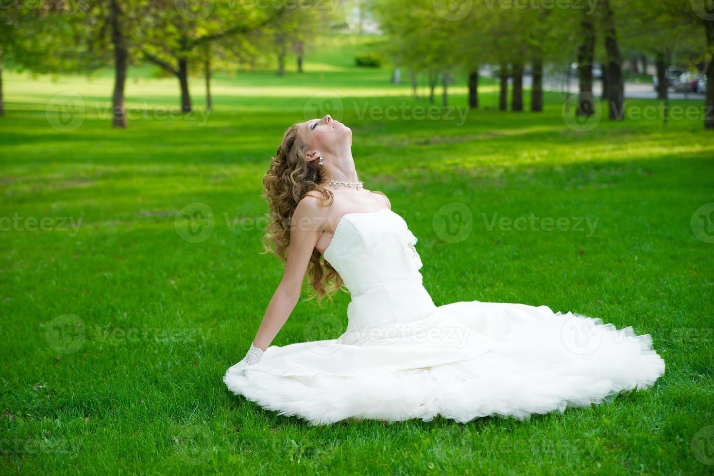 hermosa novia en vestido blanco sobre la hierba verde foto