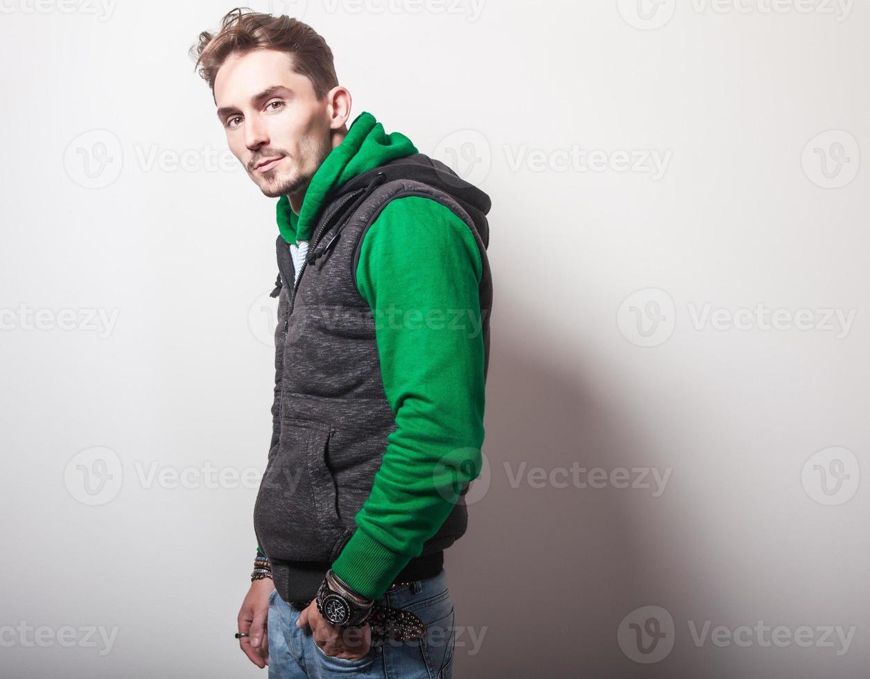 atractivo joven en chaleco gris y suéter verde. foto