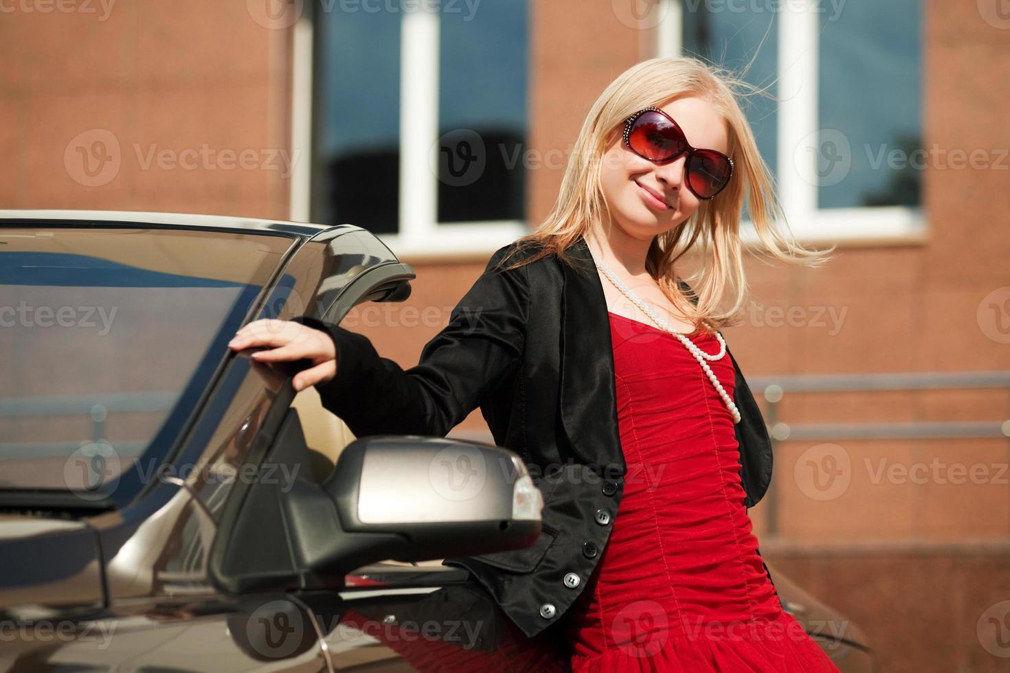 Feliz joven rubia en el coche convertible foto