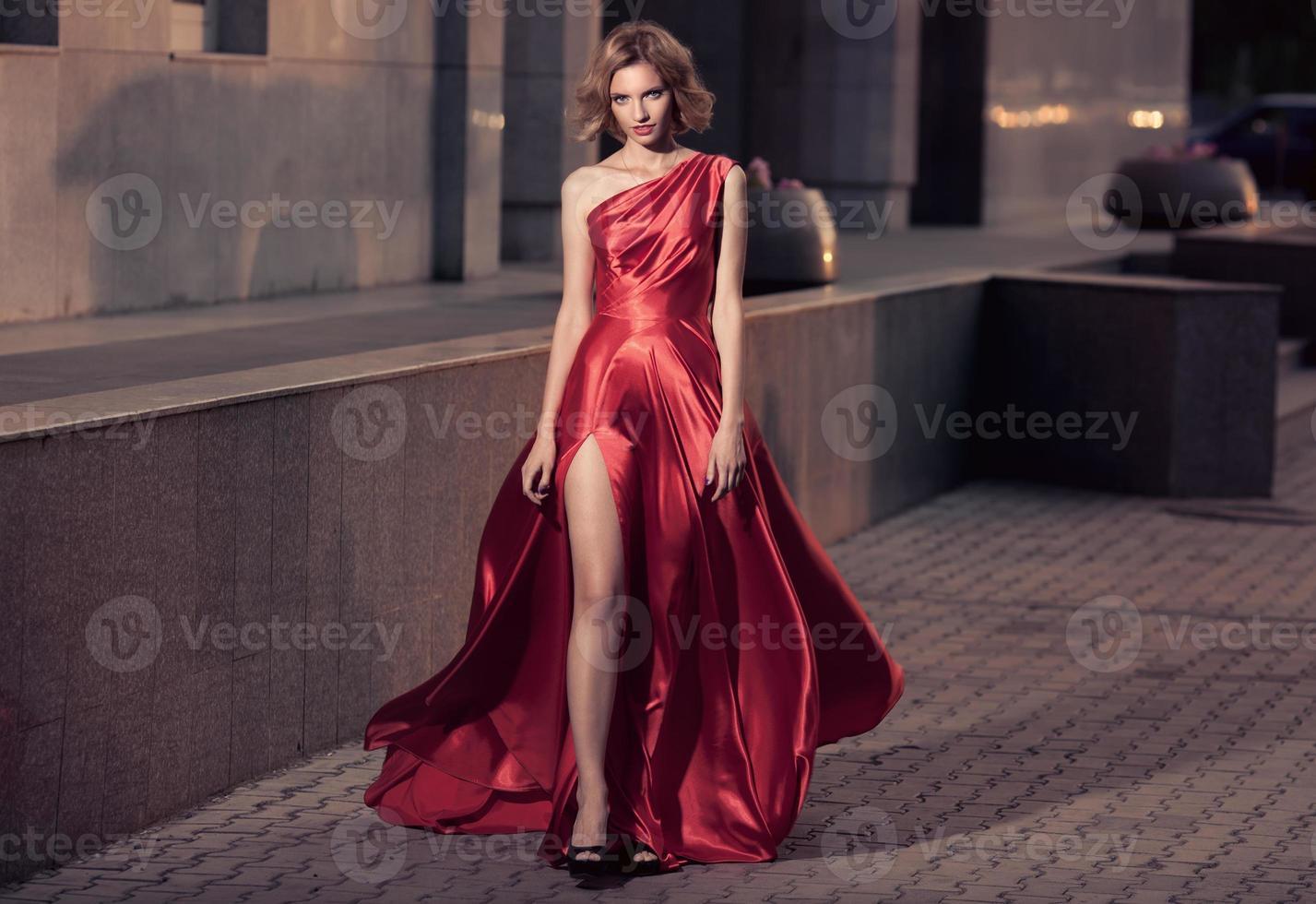 mujer hermosa joven en vestido rojo ondeando. fondo de la ciudad. foto