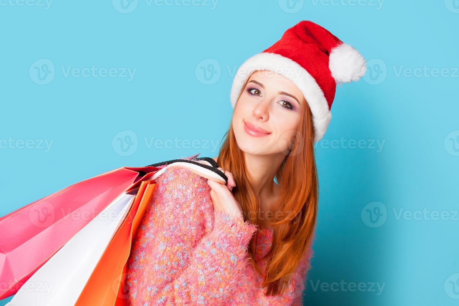 pelirroja con bolsas de la compra sobre fondo azul. foto