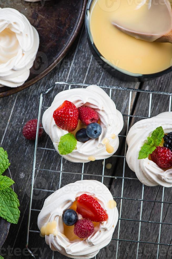 merengue pavlova casero con frutos rojos frescos foto