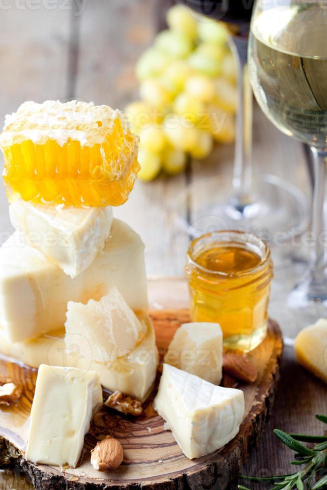 Cheese plate with honey, grape, wine in glasses photo
