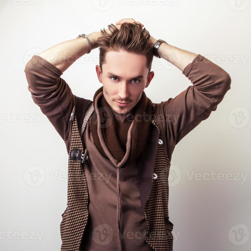 atractivo joven en una pose de suéter marrón en estudio. foto