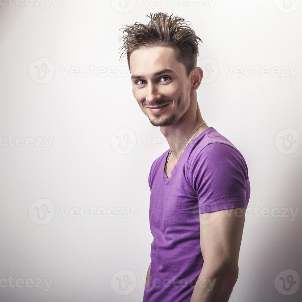 Young handsome man in violet t-shirt. photo