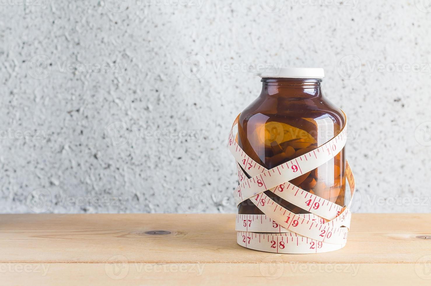 Medicine with measurement tape on wood background photo