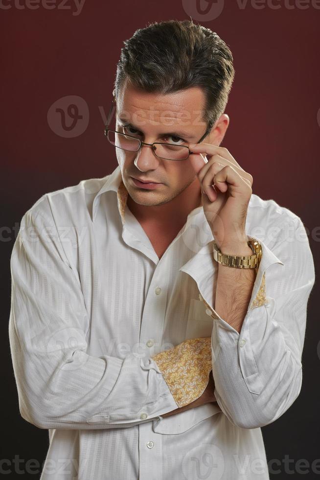 Suspicius man looking over eyeglasses photo