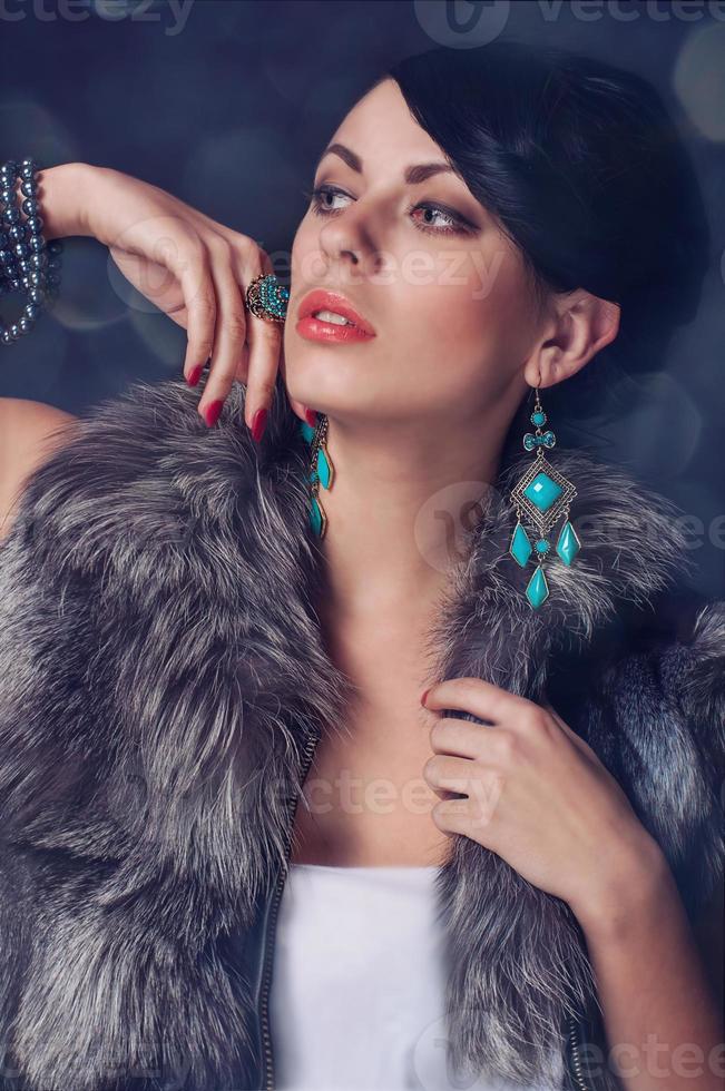 mujer joven en un abrigo de piel en aretes foto