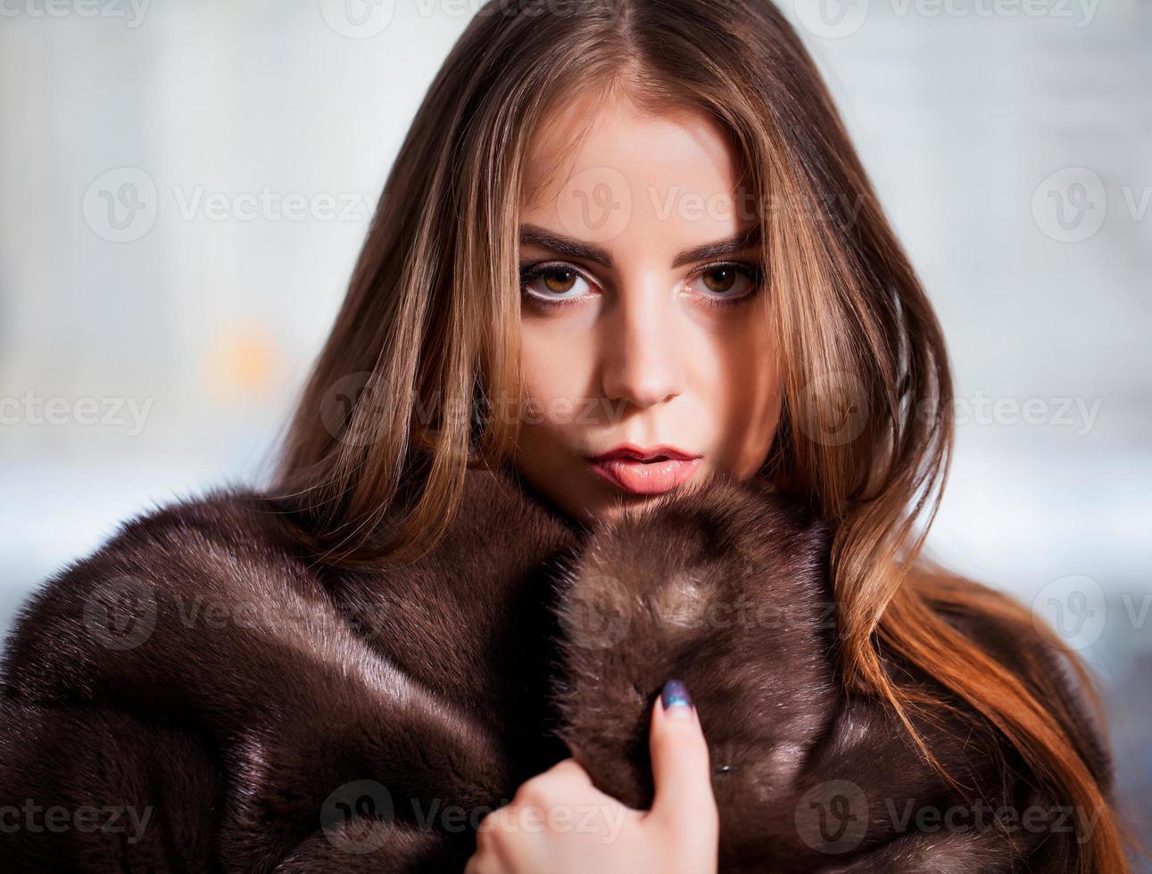 moda invierno belleza en abrigo de piel sobre negro foto