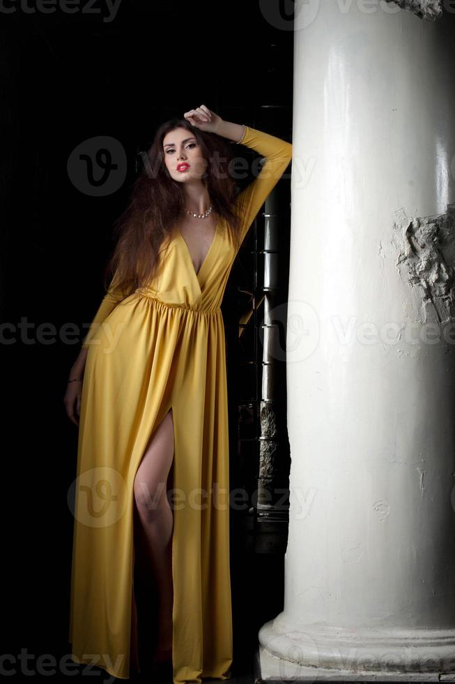 Pretty young woman posing near column photo