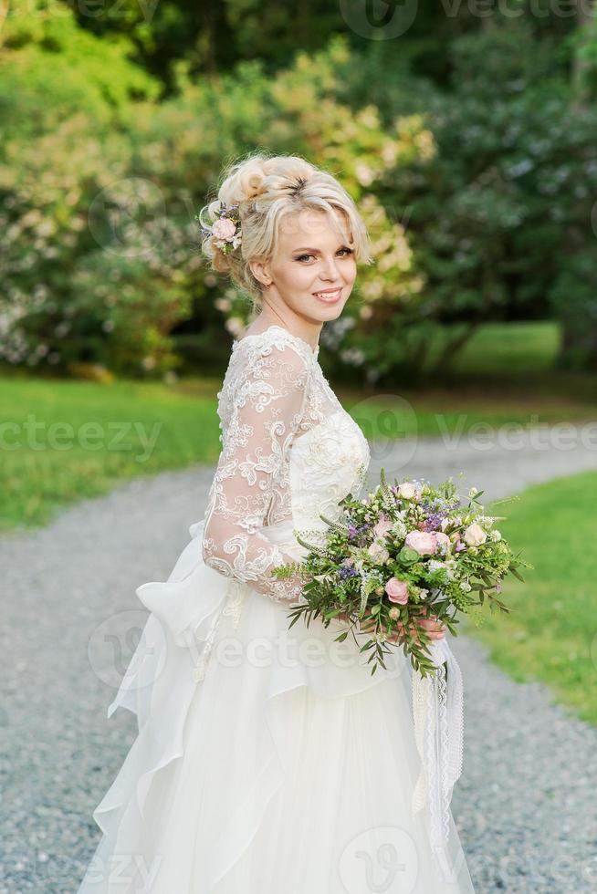 Beautiful blonde bride  in the Park whith wedding bouquet photo
