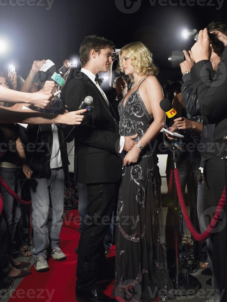 pareja que se abraza, en, alfombra roja, rodeado, por, paparazzi foto
