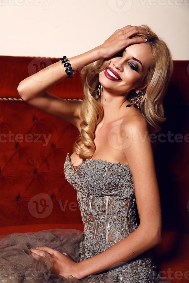 gorgeous woman with blond hair wearing luxurious sequin dress photo