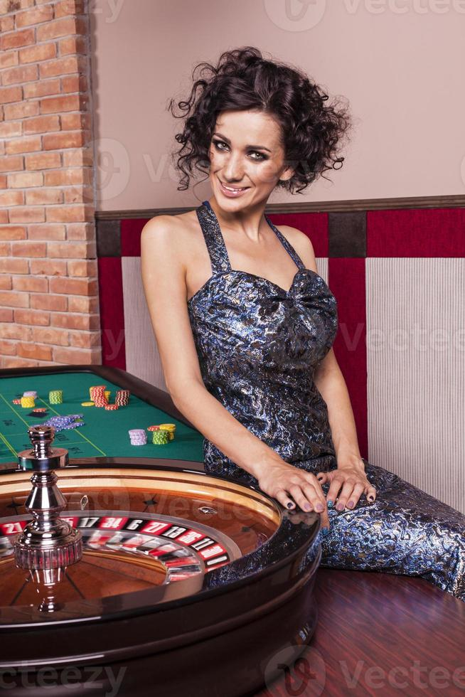 Dark hair elegant woman in casino photo