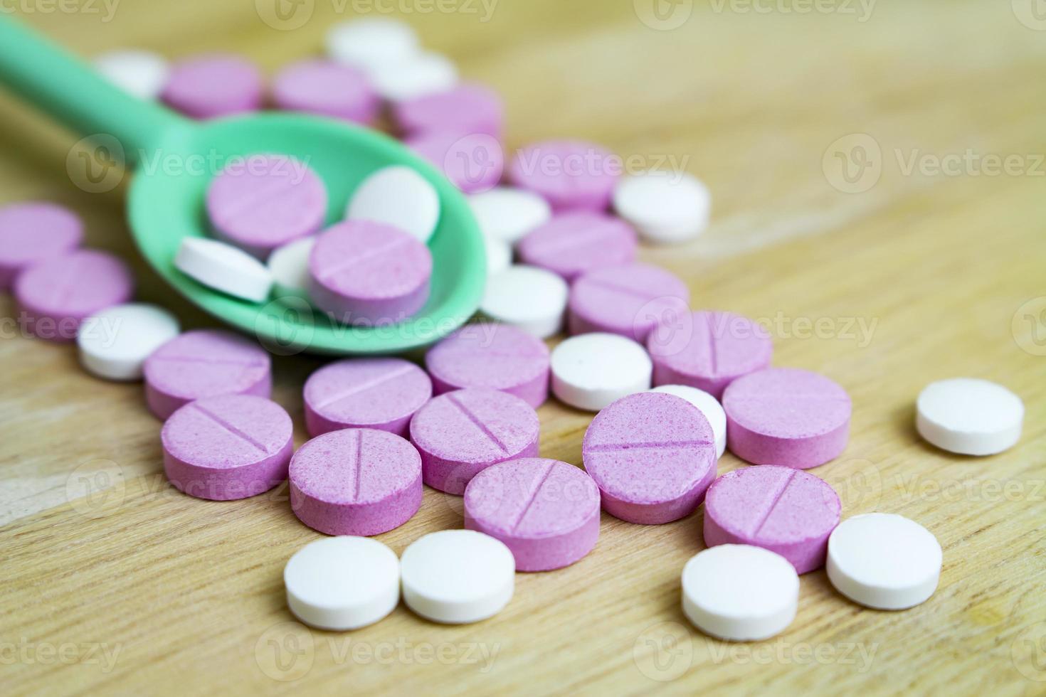 Grupo de drogas en una cuchara y una tabla de madera. foto