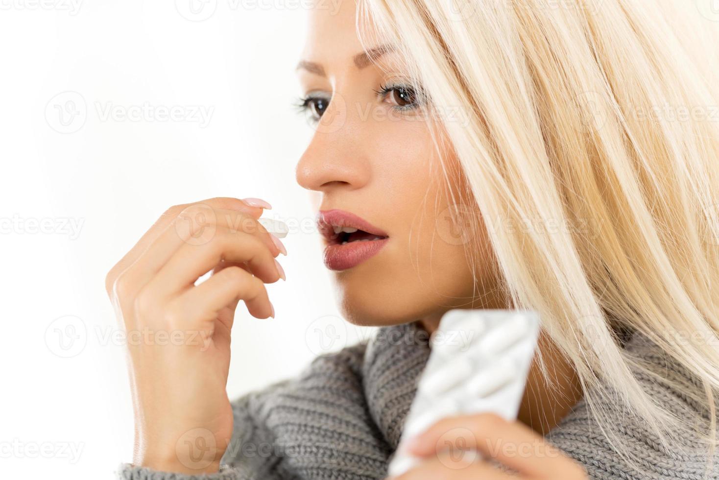 chica rubia toma una pastilla foto