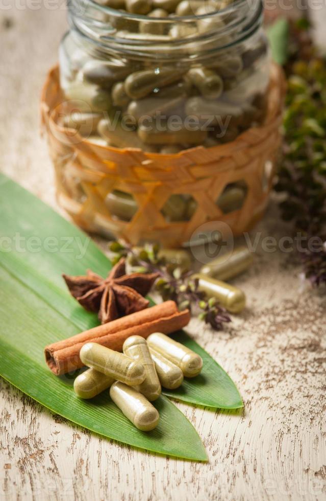 Herb capsule with green herbal leaf on wood photo