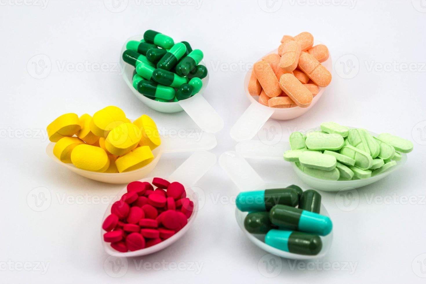 pills in tea spoon on white background photo