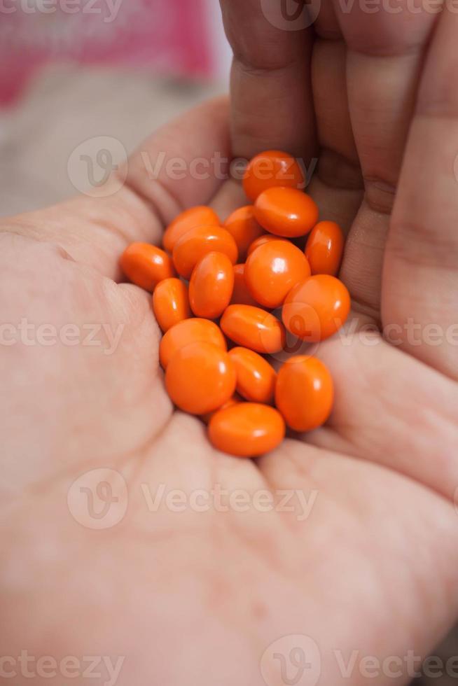 Orange pills closeup on hands. photo
