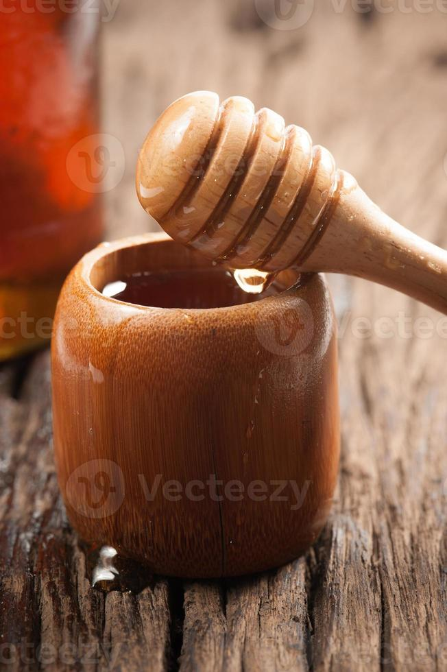 Fresh natural honey in a jar with honey spoon photo