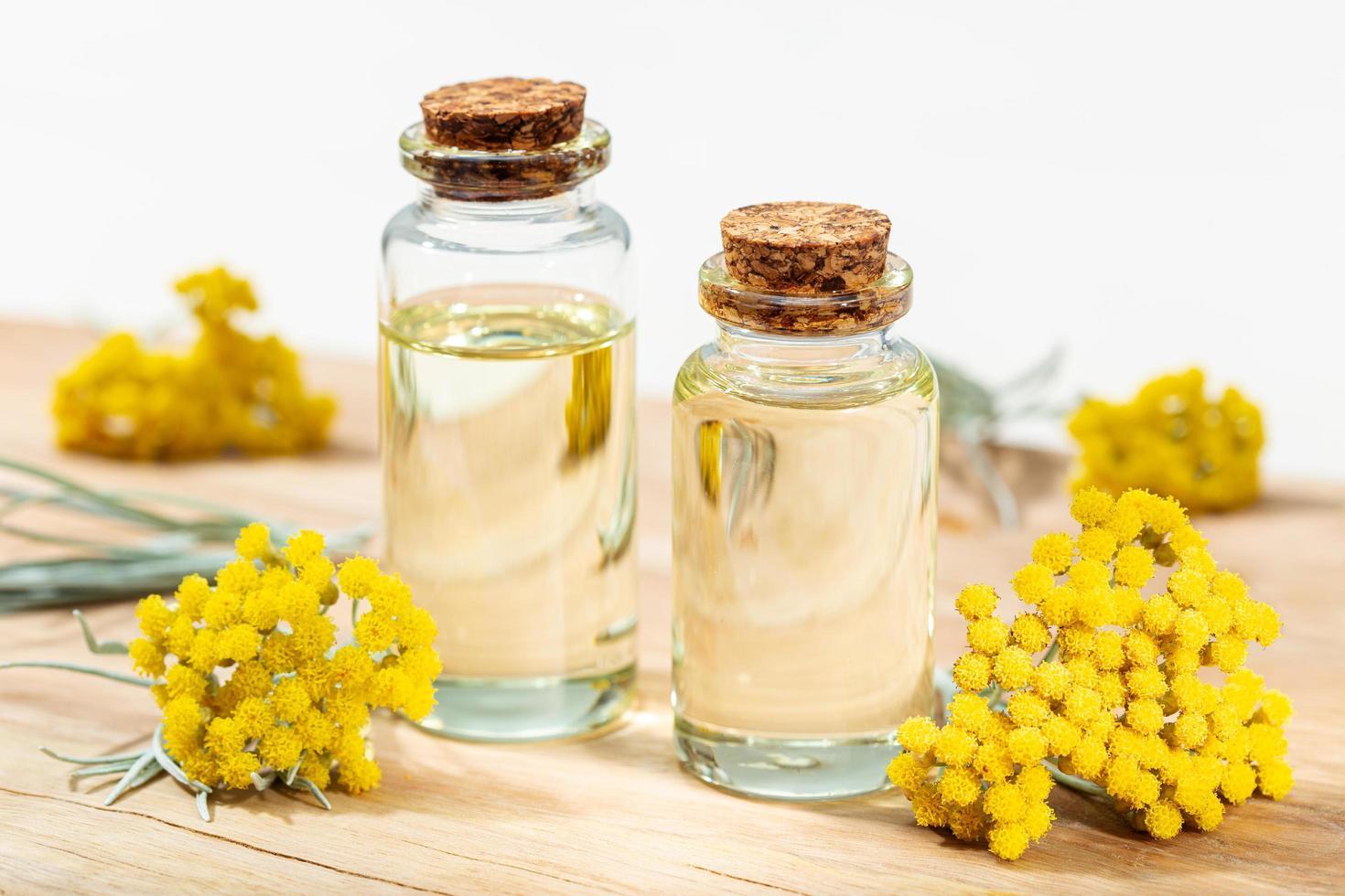 aceite esencial de helichrysum en botella de vidrio foto