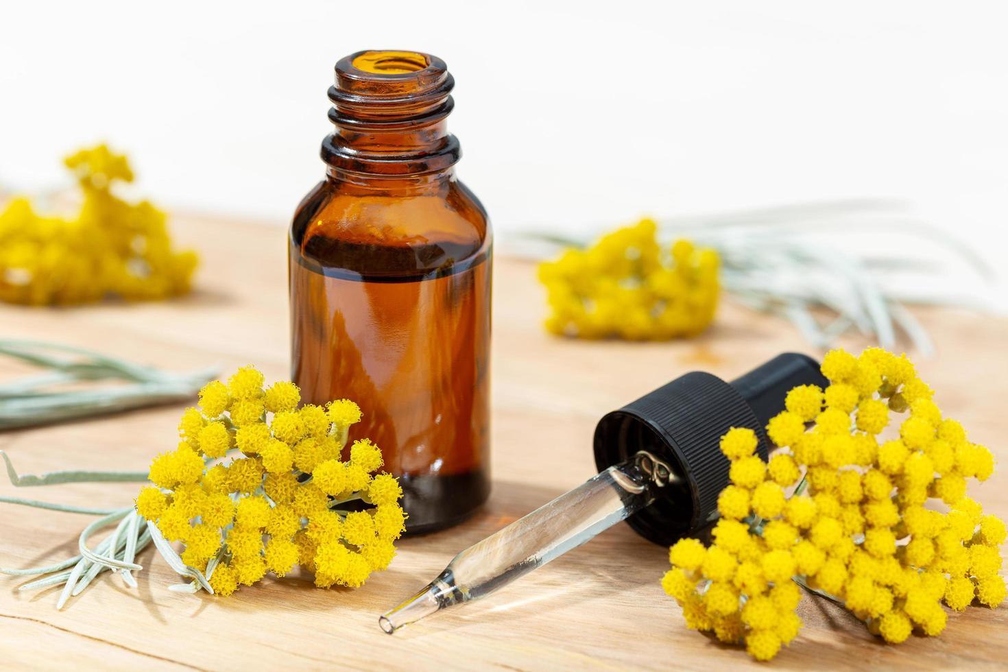 aceite esencial de helichrysum en botella ámbar y pipeta foto