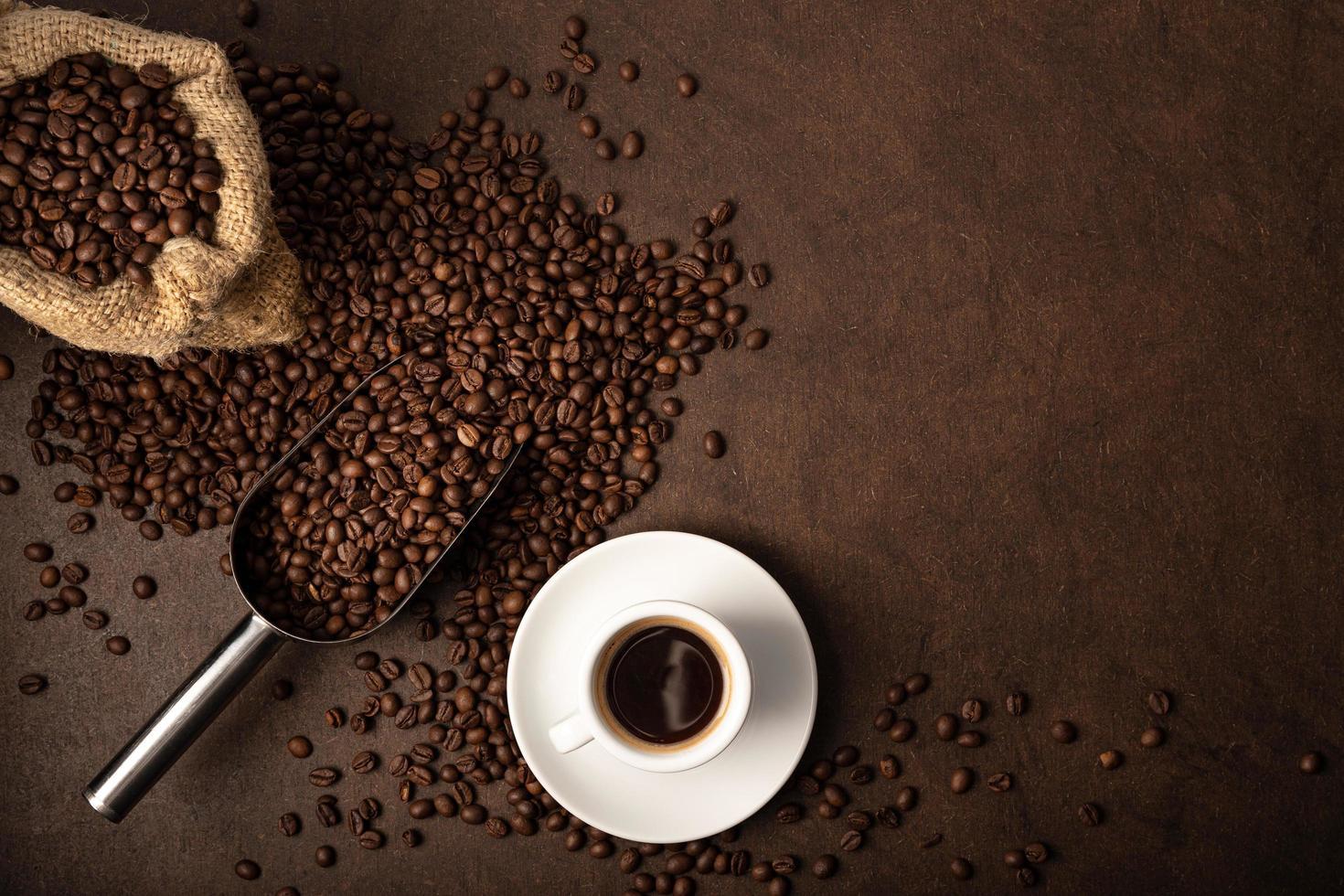 taza de café y cuchara sobre fondo marrón foto