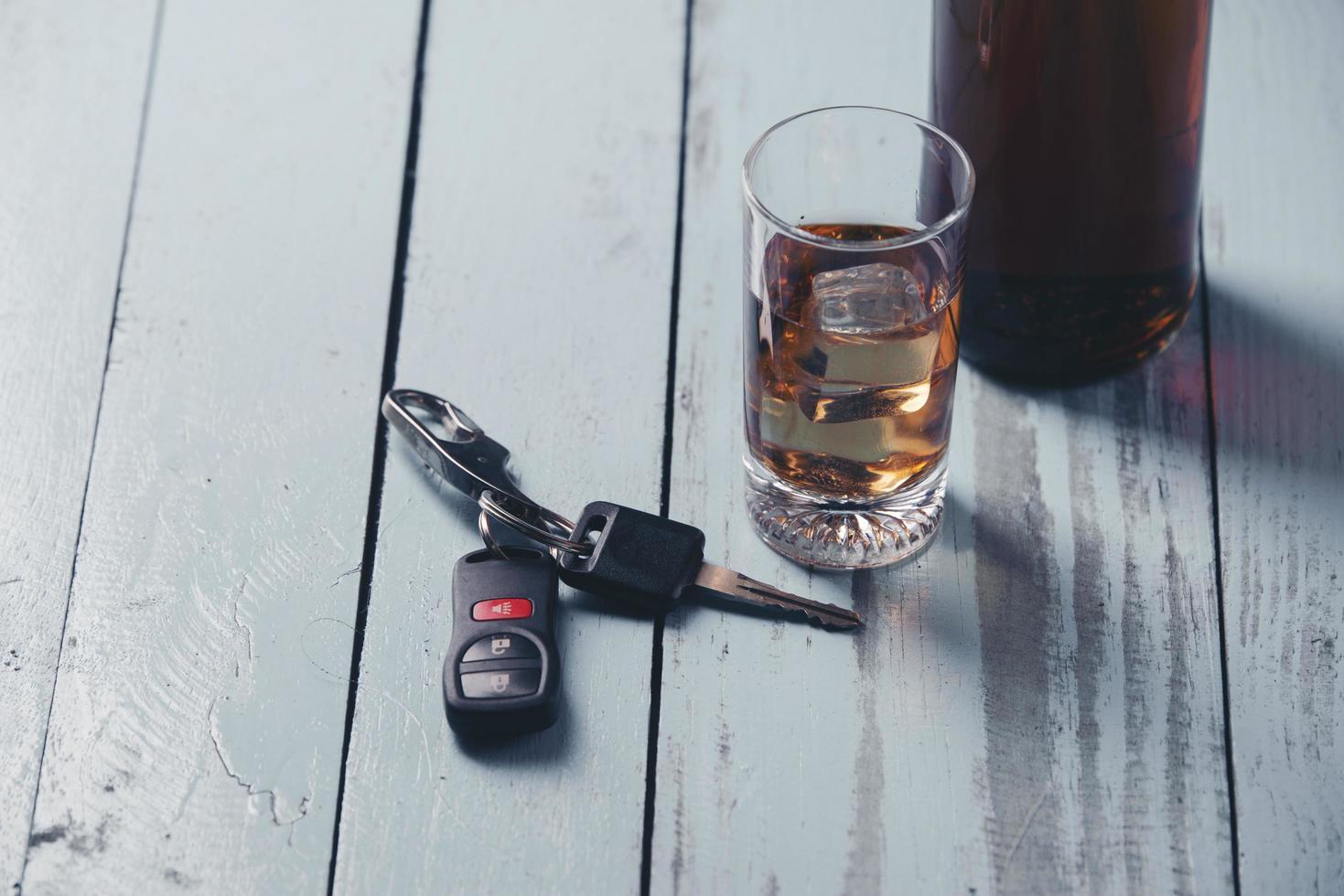 vaso, una botella de alcohol y la llave del coche. foto