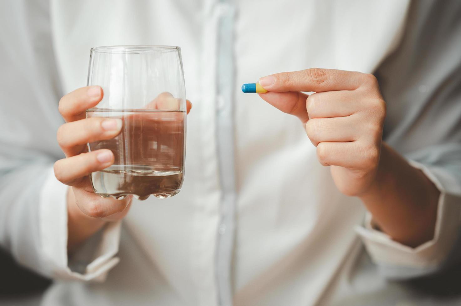 mano que sostiene la cápsula de la píldora y un vaso de agua foto