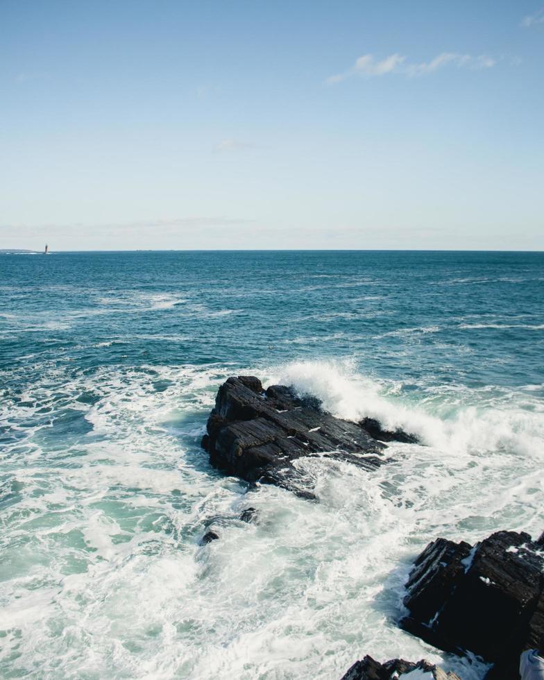 Ocean waves crashing on rocks under a blue sky photo