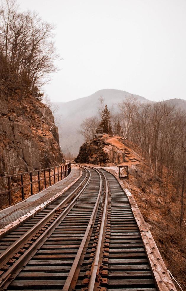 Train tracks between rocky hills photo