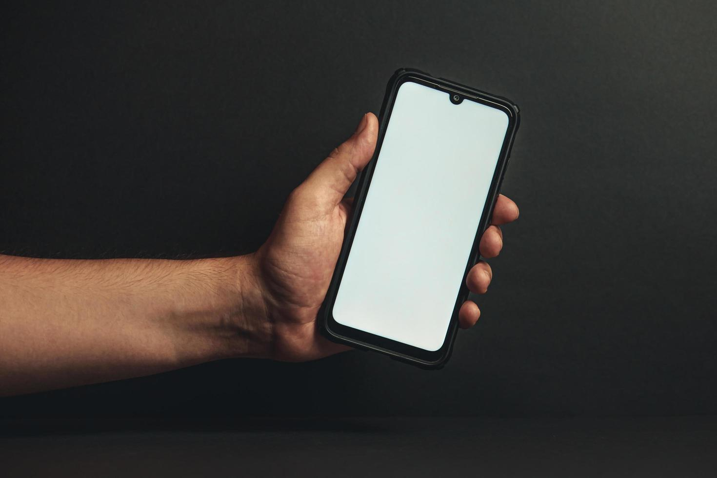 Young hand holding a phone with a white screen photo