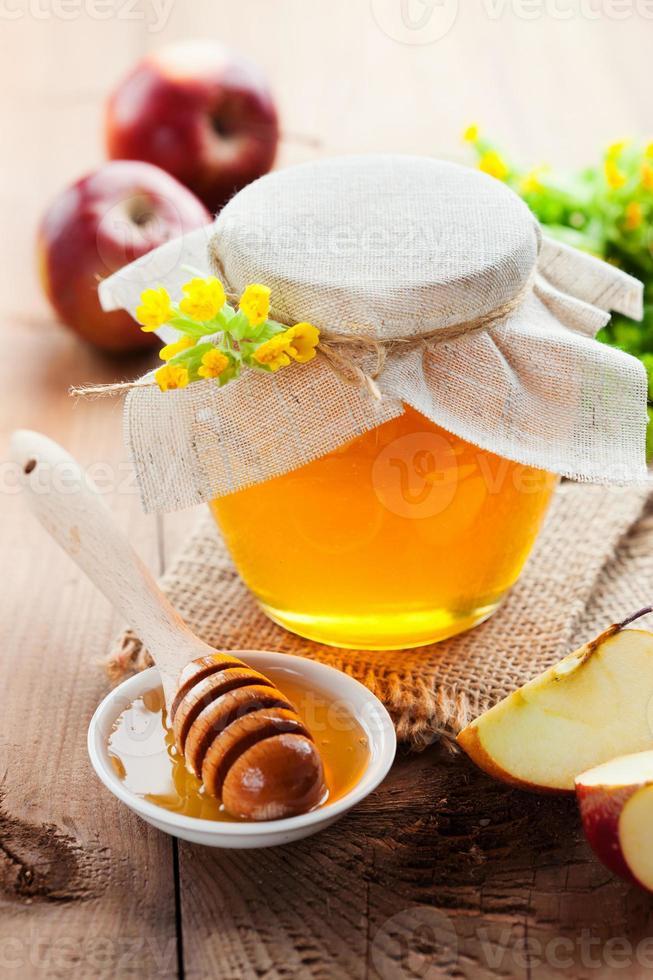 tarro de miel y palo de madera foto
