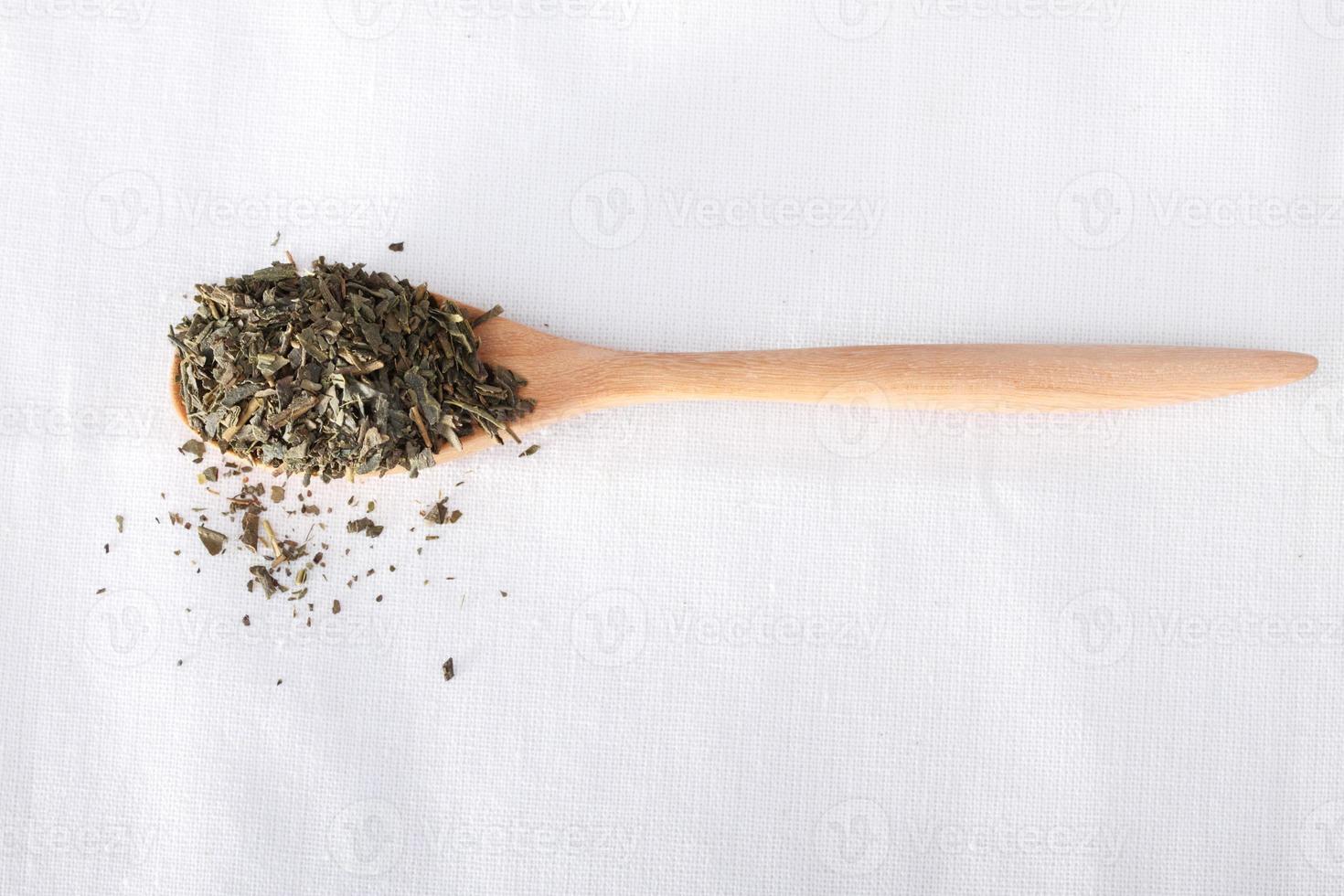 Green tea on wooden spoon photo