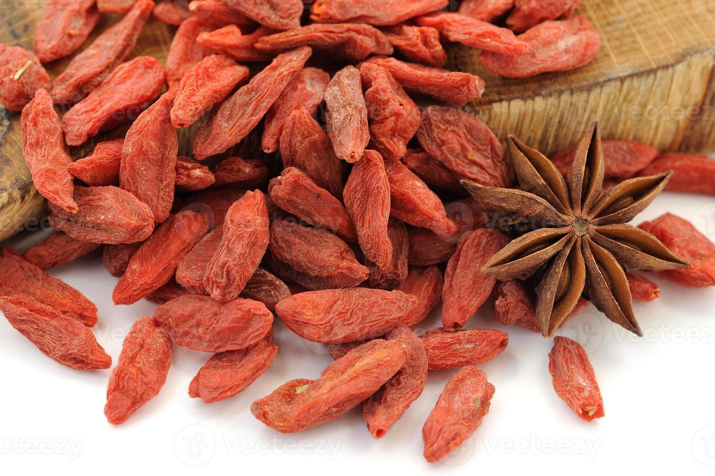 Goji berries on oak wood with star anise isolated photo