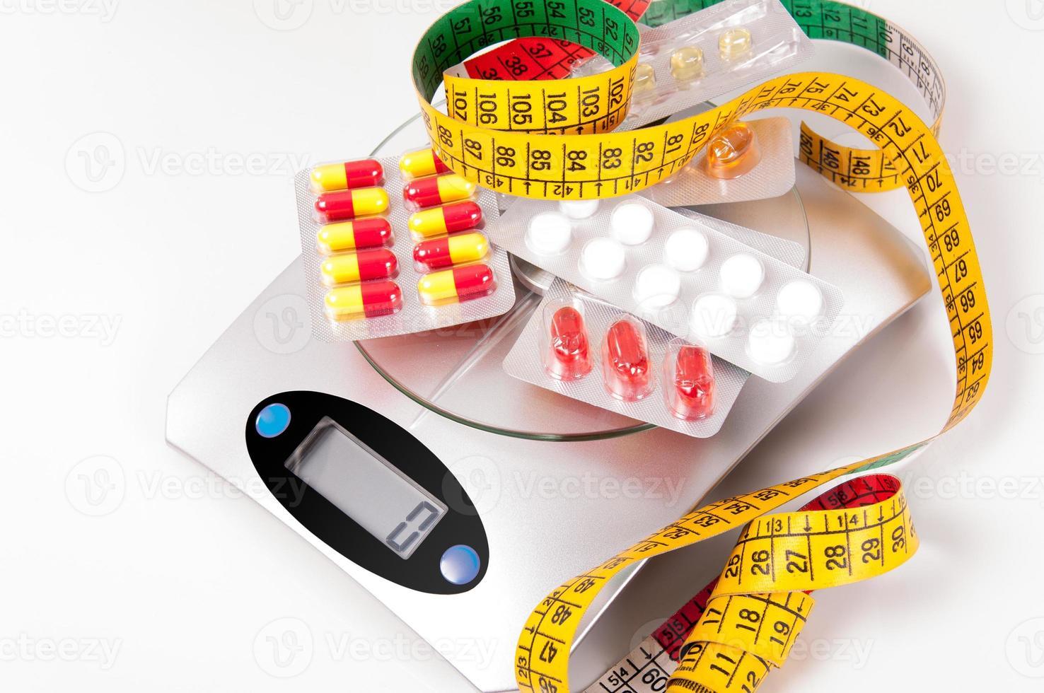 cinta métrica y medicamento sobre báscula de cocina foto