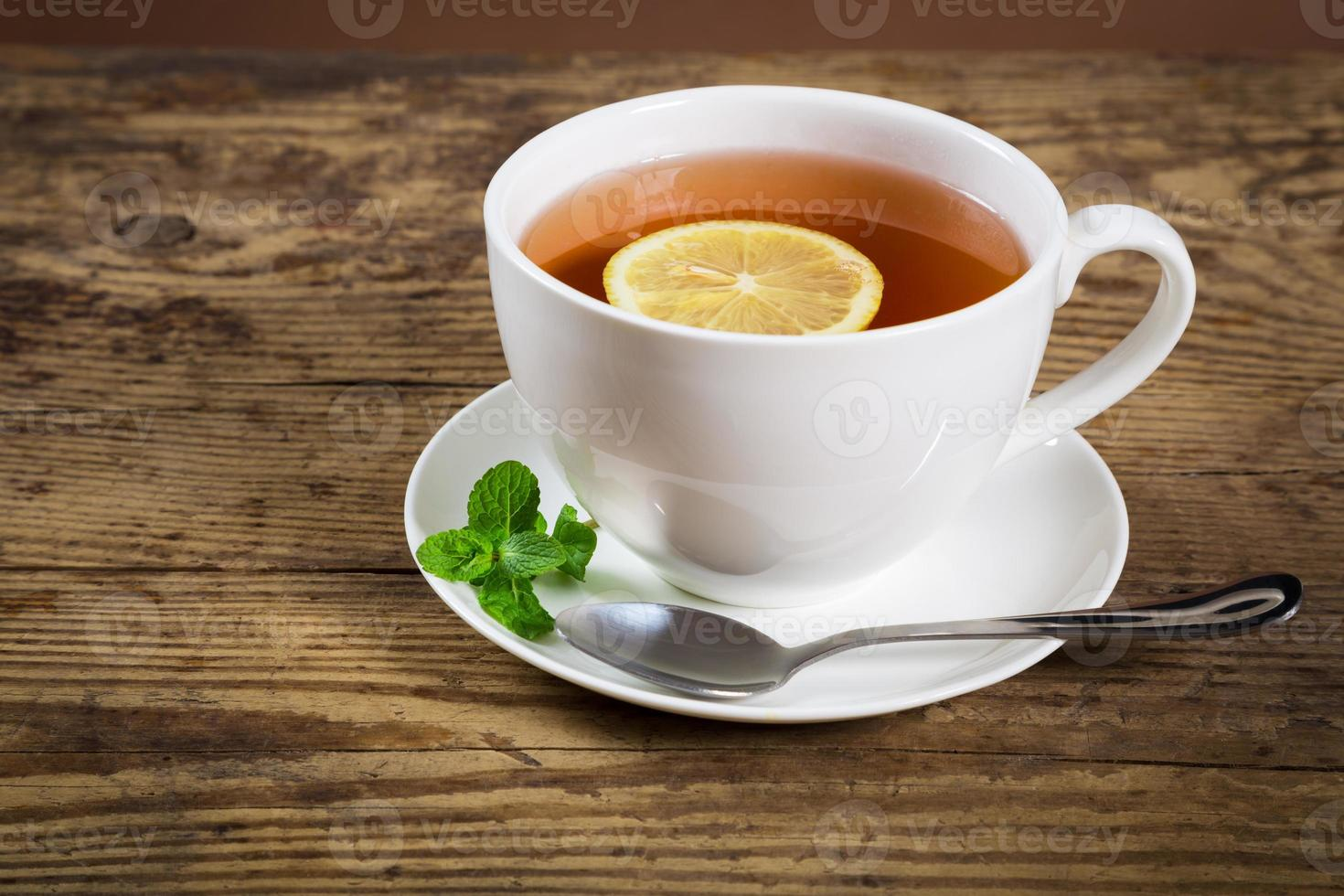 Cup of tea with mint leaf and lemon photo