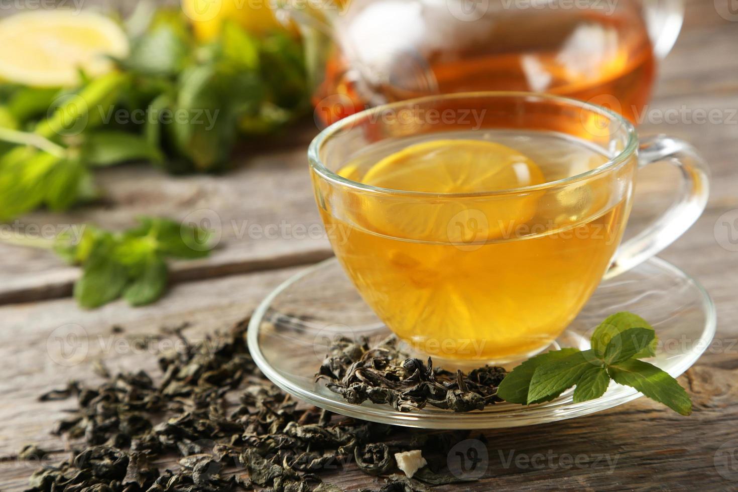 Taza con té verde y tetera sobre fondo de madera gris foto