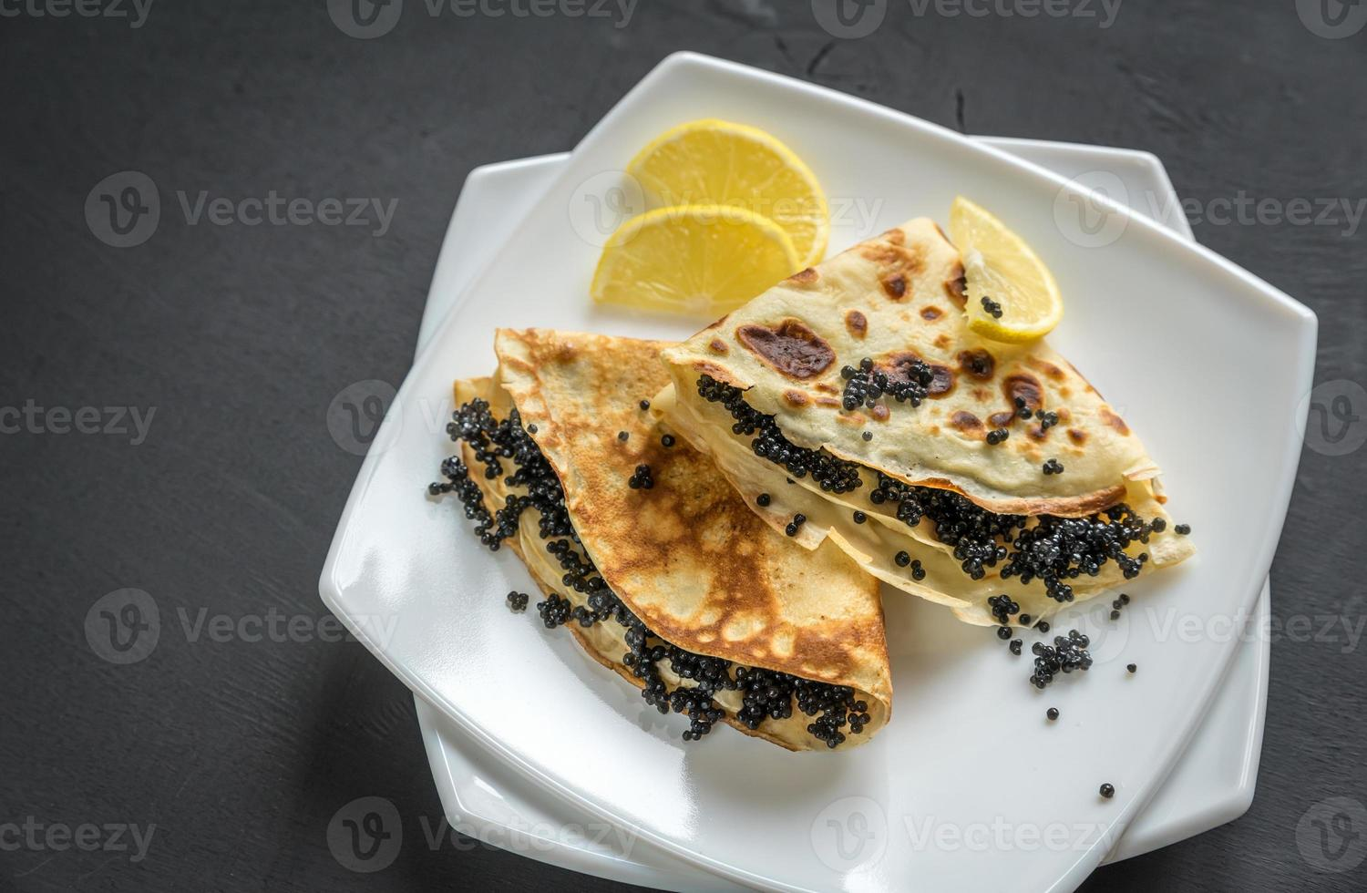 Crepes with black caviar photo