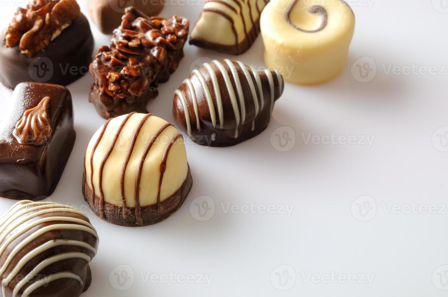 Assorted bonbons on a white table Top diagonal aligned photo