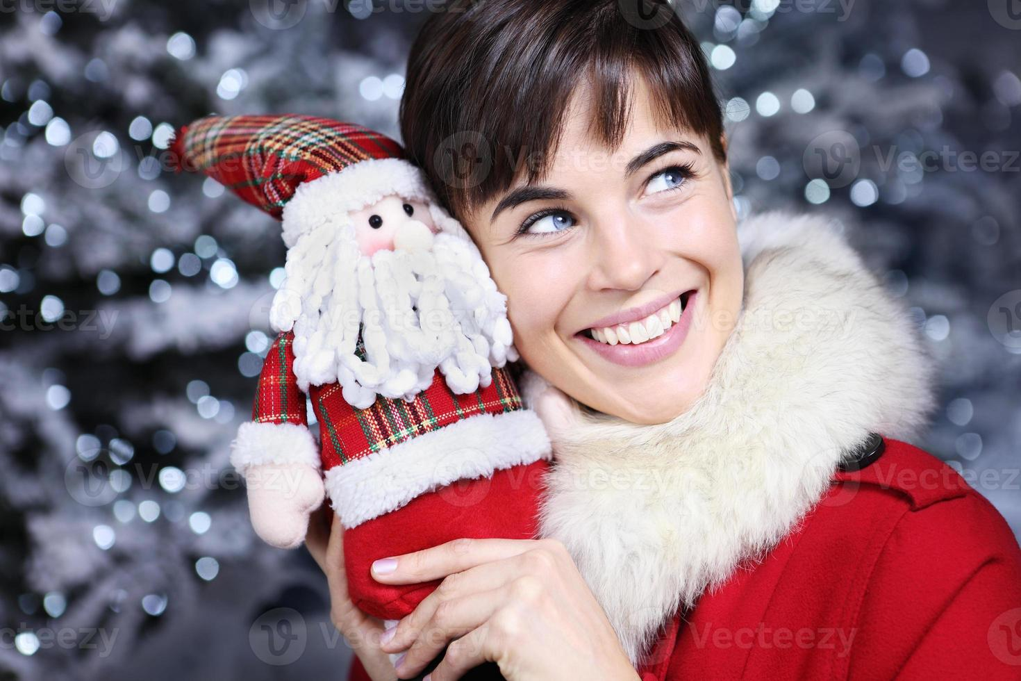 Christmas woman smiling with gift, Santa Claus toy, photo